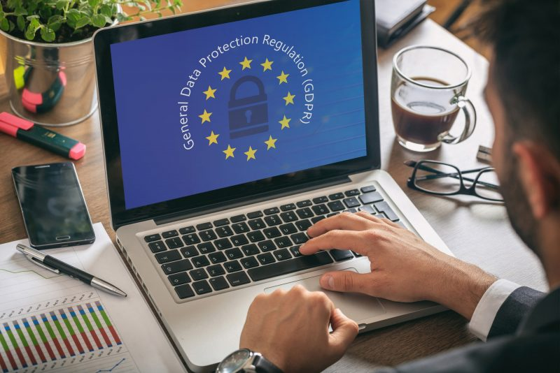 Man working with a computer, General Data Protection Regulation and European Union flag